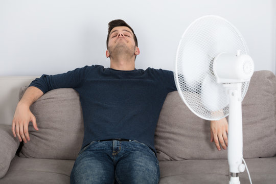 Man Sitting On Couch Cooling Off With Fan