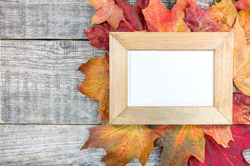 empty photo frame and colorful autumn dry leaves on grunge wooden background