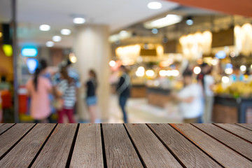 wood table on blur image people in shopping mall with bokeh.
