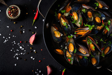 Mussels cooked in wine sauce with herbs in a frying pan on a black background. Flat lay. Top view.