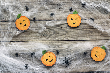 Halloween background with decorative pumpkins, creepy web and spiders on old wooden boards. Blank space for text.