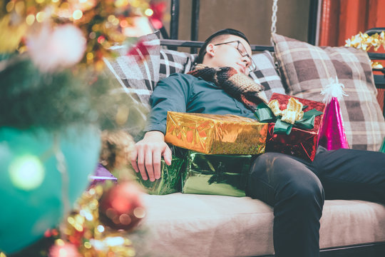 Sleeping man on a sofa after Christmas party.