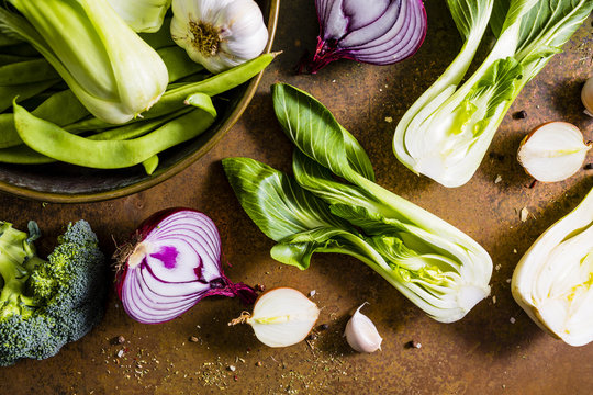Fresh and raw Chinese cabbage pak choi and other green vegetables on vintage background.