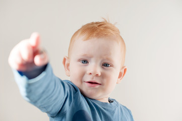 Red-haired boy in blue t-shirt points with his finger