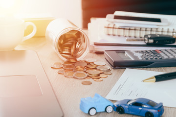 Car insurance concept:Car claim form with car toy crash on desk with Money flow out of jar coin bank ,warm tone filter