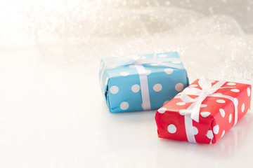 Gifts boxes with ribbons on white glitter background