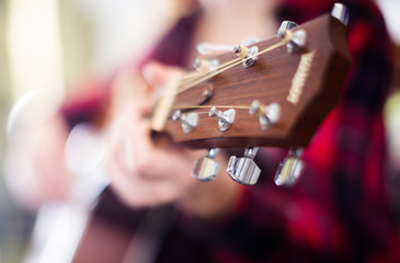 girl holding guitar. Focus on the head of guitar