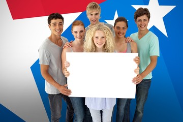 Composite image of group of teenagers holding a blank card