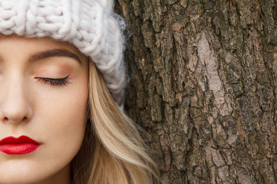 Detail half face of a beautiful young woman in winter with warm hat, who is captured in contrast with the bark of a tree. Gorgeous professional makeup, eye shadow and red lipstick.