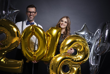 Cheerful couple holding new year's balloons .