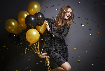 Cheerful woman with balloons laughing .