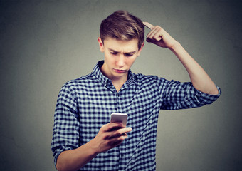 Young man dumbfounded about what he sees on cellphone, looking for solution