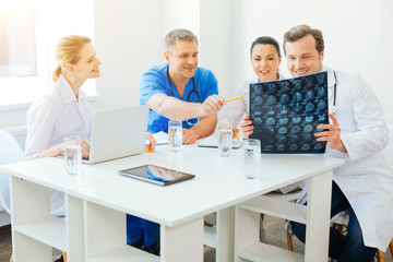 Cheerful medical professionals counseling over MRI scan image at work
