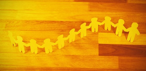 Yellow paper cutout human chain on wooden table