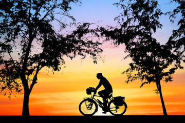 Silhouette man and bike relaxing on sunrise background