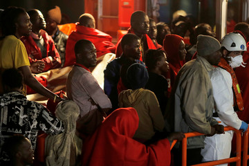 Migrants stand on a rescue boat upon arriving at a port in Malaga