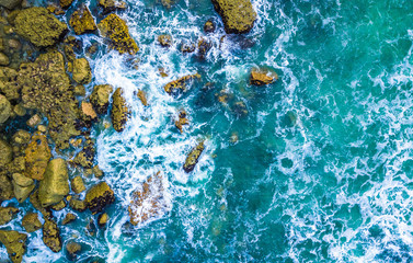Drone view of waves hitting sea shore and rocks