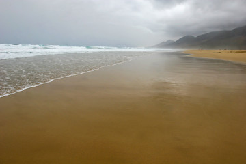 Reflection of mountains in wet sand on Cofete beach in secluded part of Fuerteventura in cloudy weather, Canary Islands, Spain