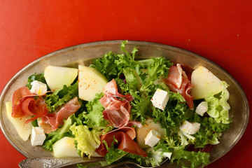 salad with prosciutto and melon slice on dish