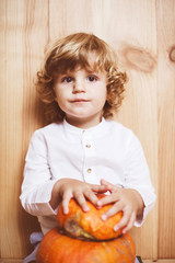 Adorable child posing with pumpkin