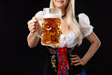 Young sexy woman wearing a dirndl with beer mug on black background.