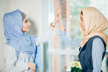 portrait of muslim woman giving high five at cafe