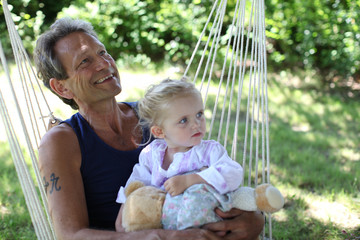 grandfather and girl sitting in a swing under a tree