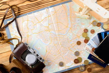 Accessories for travel. Retro vintage photo camera, travel map, passport, wallet with euro banknotes bills and wooden toy airplane, top view, flat. Holiday, tourism and travel concept background