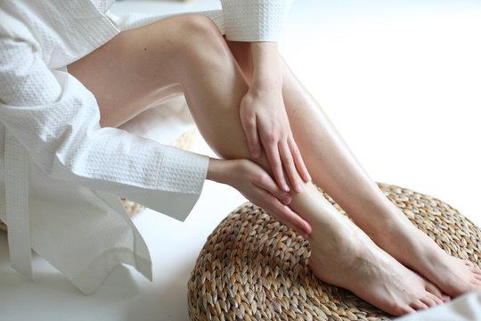 beautiful female legs, applying oil to newly waxed lower leg, spa and wellness