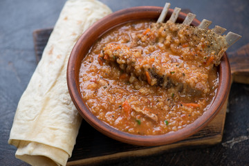 Kharcho soup with lamb meat served in a clay bowl with lavash flatbread, studio shot