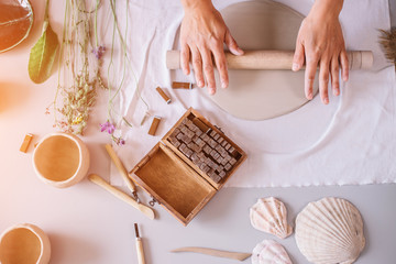 female potter master rolling up the clay on table with ceramic products