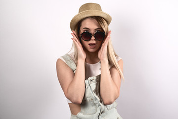 stylish young attractive woman does not believe his eyes. A surprised shocked expression dreamy. Sunglasses and hat, hands are at the cheeks, portrait on white background.