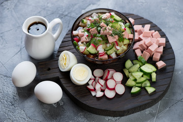 Traditional russian cold soup okroshka with some of its cooking components on a black wooden chopping board, studio shot