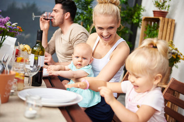Couple with baby and toddler daughters at family lunch on patio table