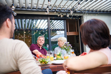 Over shoulder view of senior woman and mature man at family lunch on patio