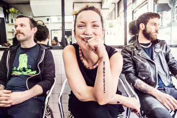 Woman with mustache tattoo on finger looking at camera smiling