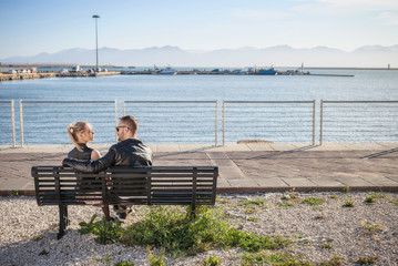 Rear view of couple face to face on bench, Cagliari, Sardinia, Italy, Europe