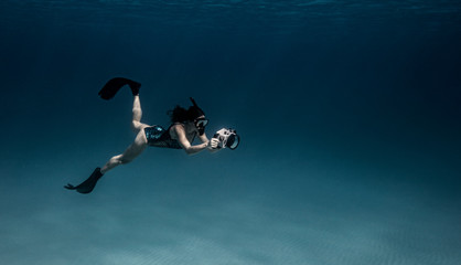 Woman diving with underwater camera
