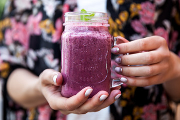 Close up woman hand with nails fashion color holding iced cold mixed berry smoothie