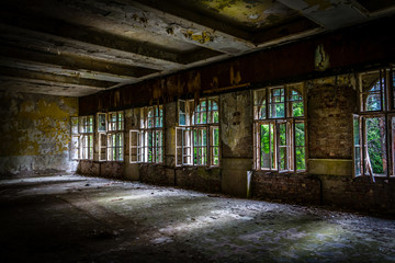 The sun's rays break the darkness in an abandoned destroyed room of an ancient building