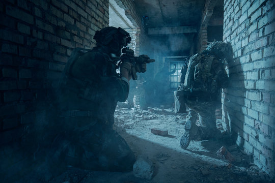 Special Forces soldiers in action. Elite squad sneak up to the enemy in a dilapidated building.They use special equipment, weapons and tactical devices.