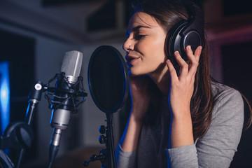 Female vocal artist singing in a recording studio