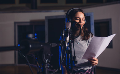Female singer with microphone and reading lyrics