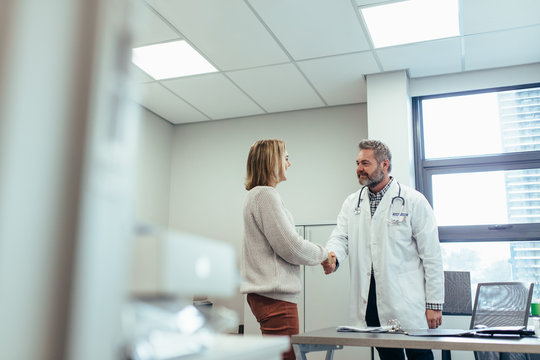 Physician shaking hands with patient in clinic