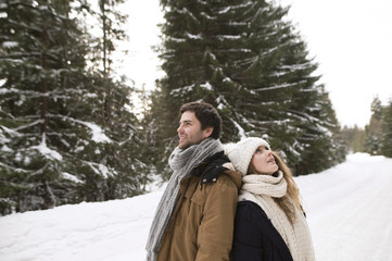 Happy young couple standing back to back in snow-covered winter landscape