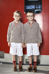Twin brothers standing in front of commuter line