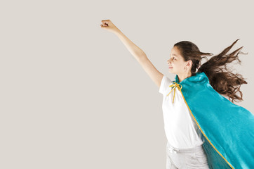 Happy cheerful female child wearing superhero clothing and making posing ready to fly on a gray background with space for text or image.