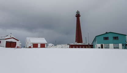 Lighthouse and houses in snow on the coast of Andenes in Norway