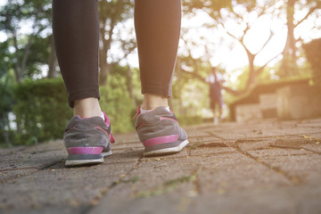 young woman runner feet running closeup on shoe,women jogging with dirty shoes in a park