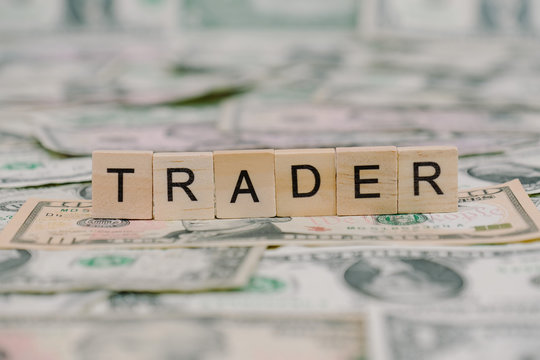 """the word """"TRADER"""" written in wooden block letters"""
